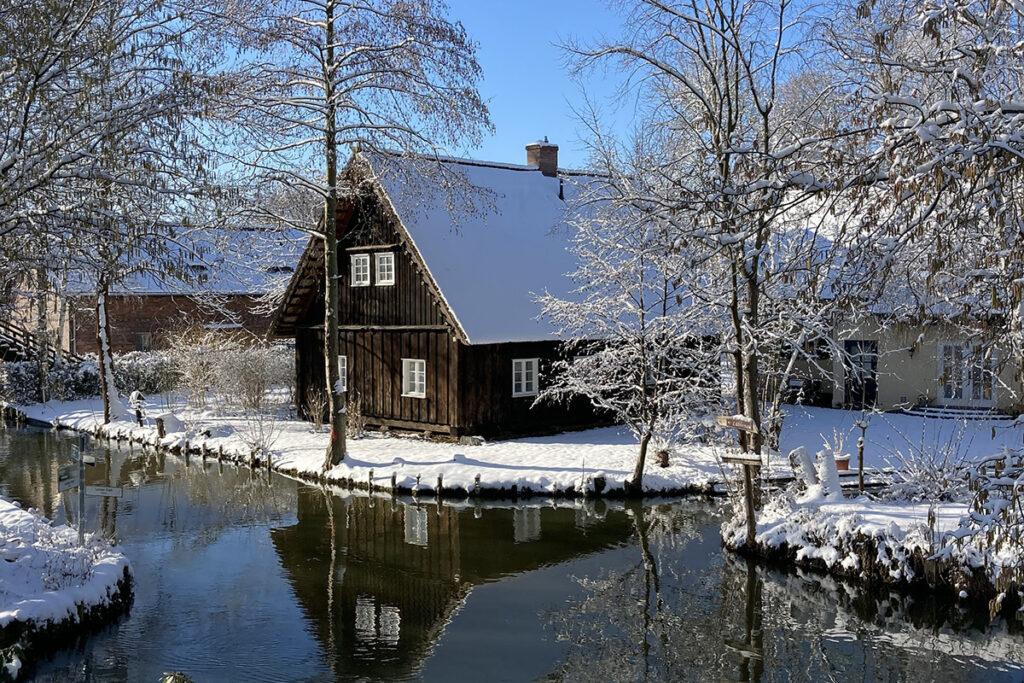 Idyllischer Wasserkanal im Winter, Spreewald-Haus mit Schnee bedeckt.