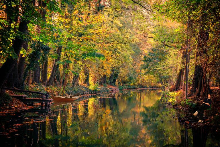 Spreewald-Kanal im Herbst mit buntem Laub, einem kleinen Steg und ein Boot